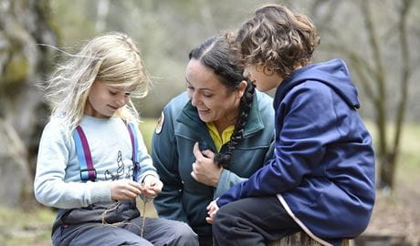 A ranger in National Parks jacket making Aboriginal tools with two small children. Photo: Adam Hollingworth