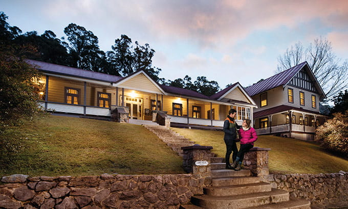 Couple on steps of Yarrangobilly Caves House in Kosciuszko National Park. Photo: M Vanderveer/OEH