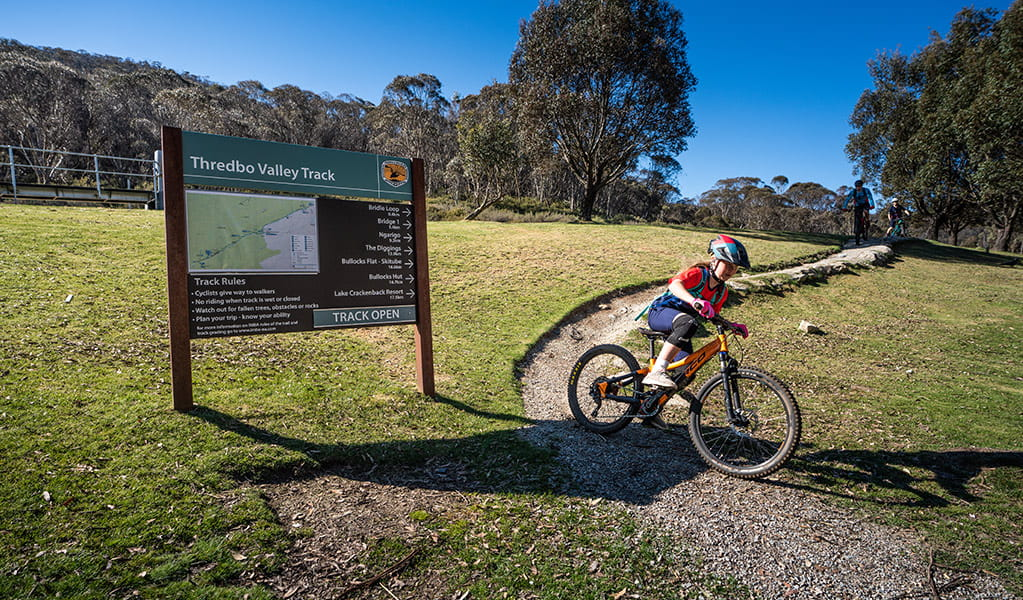 A young girl cycles past a Thredbo Valley track sign at Thredbo village in Kosciuszko National Park. Photo: Robert Mulally/DPIE