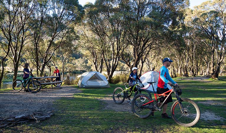 A family walk their mountain bikes past tents at Thredbo Diggings campground in Kosciuszko National Park. Photo: Robert Mulally/DPIE