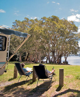 Couple sitting by the lake, Mungo Brush campground, Myall Lakes National Park. Photo: John Spencer/OEH