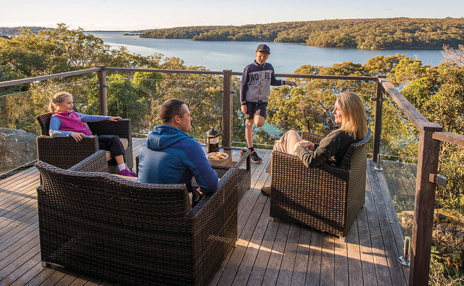 A family of 4 sit on the deck at Hilltop Cottage, overlooking the Hacking River, in Royal National Park. Photo: John Spencer/DPIE