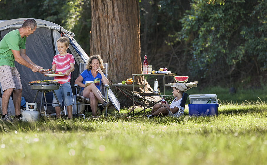 A family relaxes by their tent at the Basin campground, Ku-ring-gai Chase National Park. Photo: David Finnegan/OEH