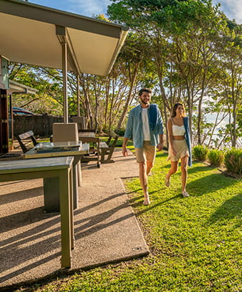 A man and woman walk in front of the verandah at Mildenhall Cottage in Cape Byron State Conservation Area. Photo: John Spencer/DPIE