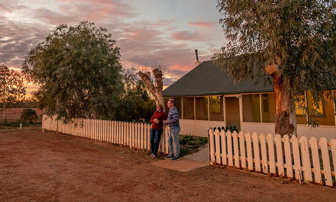 A couple watch an outback sunset outside Mount Wood Homestead, Sturt National Park. Photo: John Spencer/DPIE