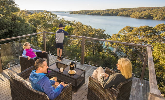 A family relax on the balcony at Hilltop Cottage, Royal National Park. Photo: J Spencer/OEH.
