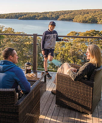 A family relax on the balcony at Hilltop Cottage, Royal National Park. Photo: John Spencer/DPIE
