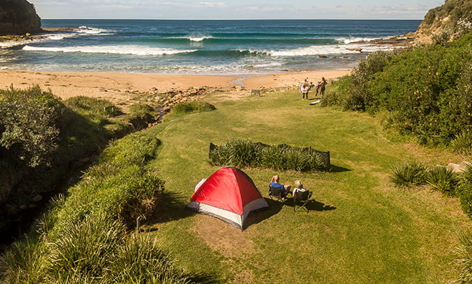 Aerial view of a red tent at Little Beach campground in Bouddi National Park. Photo: John Spencer/DPIE