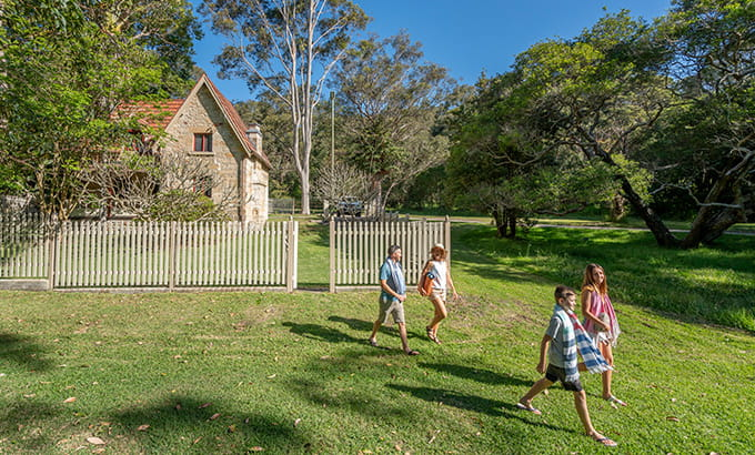 A family of four walk in front of Gardeners Cottage, Sydney Harbour National Park. Photo: John Spencer/DPIE