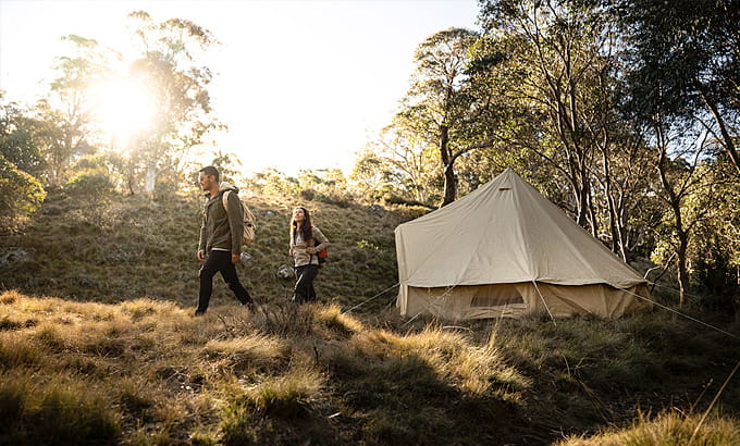 A couple walk past a tent at Junction Pools campground, Barrington Tops National Park. Photo: Robert Mulally/DPIE