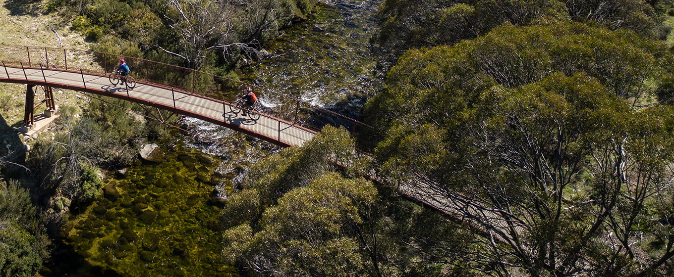 Aerial view of two mountain bike riders crossing a bridge over the Thredbo River on Thredbo Valley track, Kosciuszko National Park. Photo: Robert Mulally/DPIE
