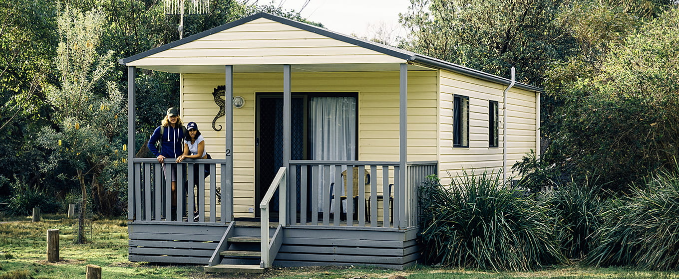 Couple standing on verandah of Pretty Beach cabins in Murramarang National Park. Photo: Melissa Findley/OEH