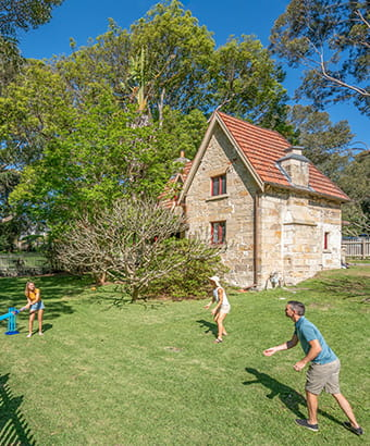 A family of four play cricket on the lawn in front of Gardeners Cottage, Sydney Harbour National Park. Photo: John Spencer/DPIE