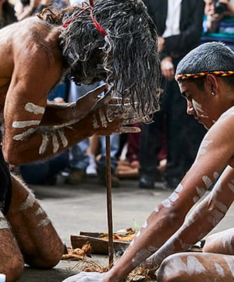 2 men share an Aboriginal cultural technique of fire starting with visitors. Flash Point Labs s © Tribal Warrior