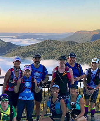 A group of runners stand in front of sweeping mountain and valley views. Photo credit: Tony Williams © Blue Mountains Fitness