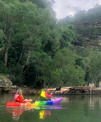 2 people kayaking near a historic shipwreck on the Lower Hawkesbury River. Photo credit: Daniel Morrison © River Adventures