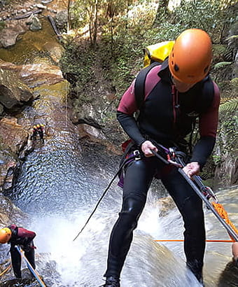 A pair of wetsuit-clad climbers use ropes to abseil past a waterfall. Photo: James Waddell © Eagle Rock Adventures