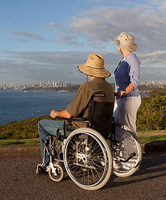 A man in a wheelchair and companion enjoy views at North Head, Sydney Harbour National Park. Photo: David Finnegan