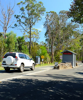A car passes the park entry booth at Ku-ring-gai Chase National Park. Photo: E Sheargold/OEH