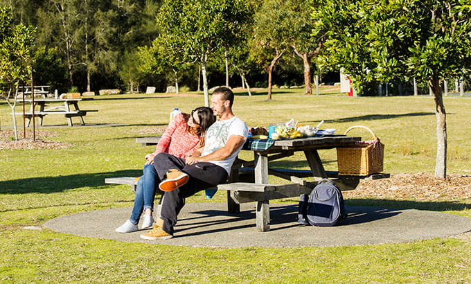 A couple sit together at a picnic table, Bonnie Vale picnic area, Royal National Park. Photo: Simone Cottrell/OEH