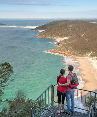 A couple enjoy views from Tomaree Head summit walk, Tomaree National Park. Photo: J Spencer/OEH.