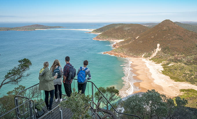 Four people stand at a lookout on Tomaree Head summit overlooking the coast, in Tomaree National Park. Photo: John Spencer/DPIE