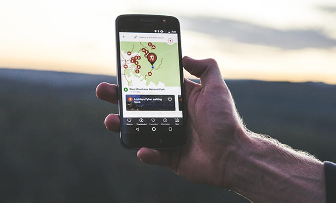 A man uses the NPWS app on a mobile phone at sunrise in Blue Mountains National Park. Photo: Daniel Parsons/DPIE