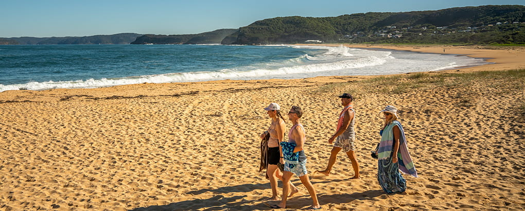 A group of people walking along Putty Beach in Bouddi National Park. Photo: John Spencer/DPIE