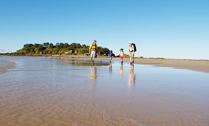 A family of 4 walks along the beach of Sandon River at low tide, Yuraygir National Park. Photo: Debrah Novak/DPIE