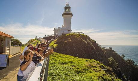 A group of people with binoculars watch for whales, with Cape Byron lighthouse in the background.  Photo credit: John Spencer © DPIE