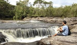 A man sits by a waterfall in Heathcote National Park. Photo: John Yurasek/OEH
