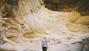 A young man looking with awe at the sandstone caves in Pilliga National Park. Photo: Harrison Candlin