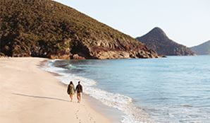 A couple walking along the beach at Tomaree National Park. Photo: Tim Clark/DPIE