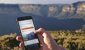 Hand holding a phone with NSW National Parks app on screen. Photo: Branden Bodman/DPIE