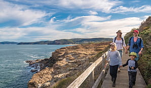 A family walk a boardwalk section of Bouddi coastal walk, Bouddi National Park. Photo: John Spencer/OEH.