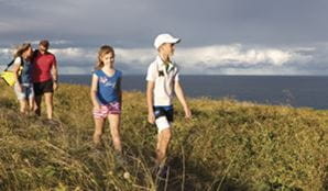 A family walk along a coastal path on Muttonbird Island Nature Reserve. Photo: R Clearly Seen Australia