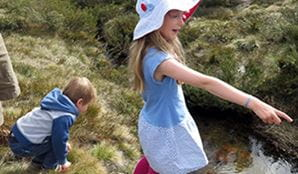 Kids looking in the river in Kosciuszko National Park. Photo: K Cooper/OEH