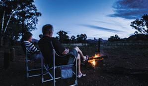 A couple sit by a campfire at Camp Blackman, in Warrumbungle National Park. Photo: Simone Cottrell/OEH