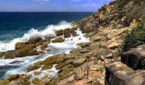 Large swell crashing over rocks and into Mermaid Pools in Arakoon National Park. Image credit: Shane Robinson © DPIE