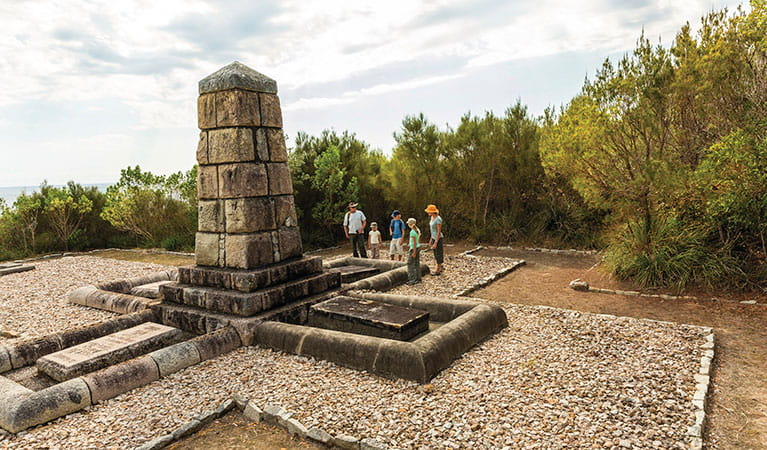 Visitors standing by the monument tribute at Arakoon National Park. Photo: David Finnegan/DPIE