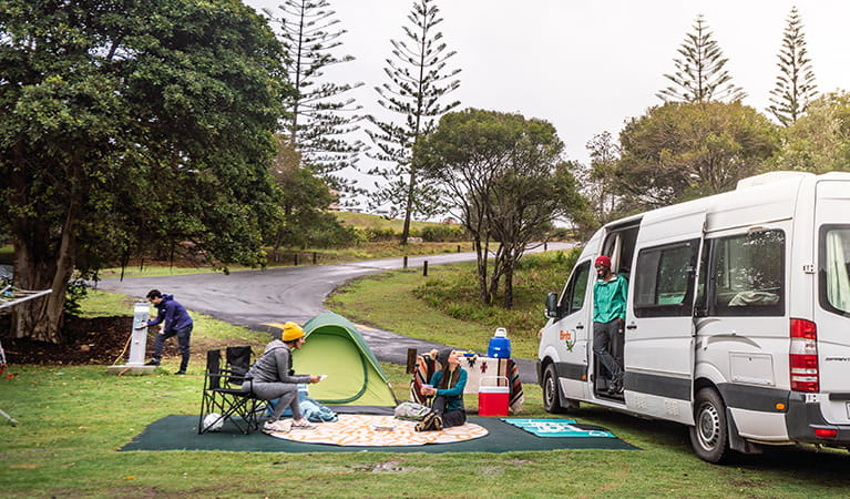Campers picnicking next to their campervan at Trial Bay Gaol campground, Arakoon National Park. Photo: Rob Mulally/DPIE