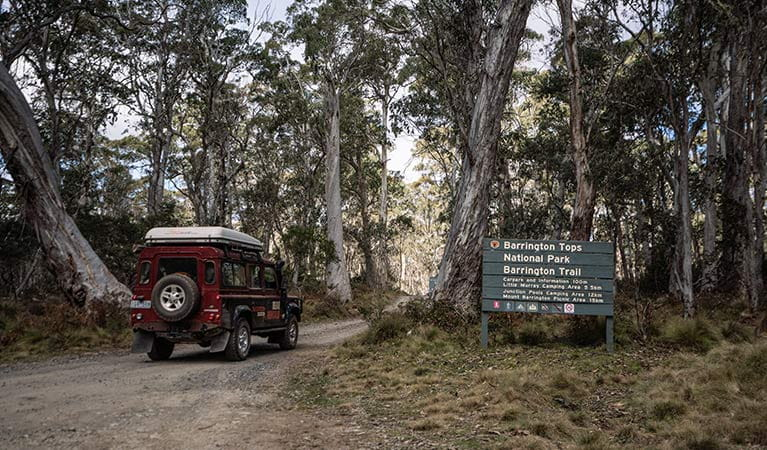 A 4WD vehicle drives past a sign on Barrington trail, Barrington National Park. Photo: Robert Mulally/OEH.