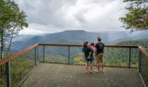 A family of 3 taking in the view from Devils Hole lookout in Barrington Tops National Park. Photo: John Spencer/DPIE