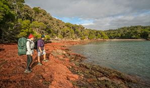 Light to Light walkers standing on the red rocks at Bittangabee Bay. Photo: John Spencer/OEH