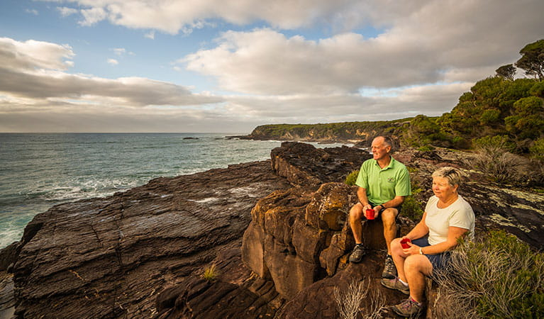 People relaxing on ocean cliffs at Bittangabee campground, Ben Boyd National Park. Photo: J Spencer/OEH