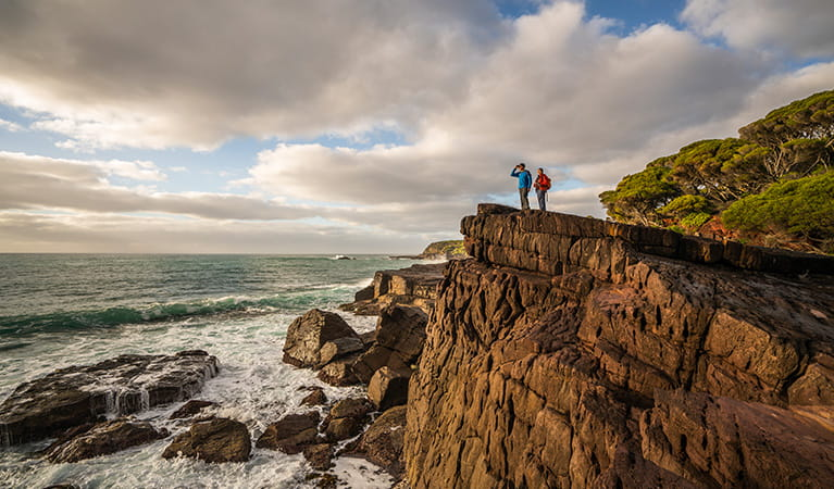 Bushwalkers on cliffside, Bittangabee campground, Ben Boyd National Park. Photo: J Spencer/OEH