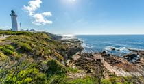 Distant view of Green Cape Lighthouse and outbuildings set on rugged coastal terrain with rocky reefs. Photo: John Spencer © DPIE