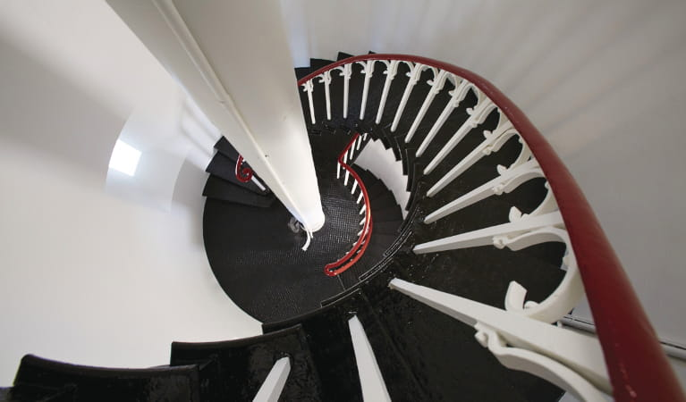 Black steel spiral staircase with white wrought iron railing and polished wood banister. Photo: Nick Cubbin © DPIE