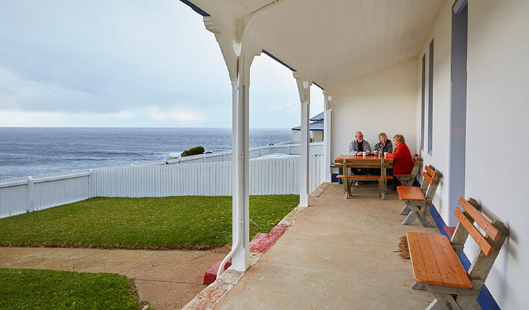 Friends sitting on the verandah with views of the ocean at Green Cape Lightstation Keeper's Cottage. Photo: N Cubbin/OEH