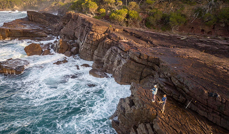2 people fishing from the top of the rocks near Bittangabee Bay. Photo: John Spencer/DPIE